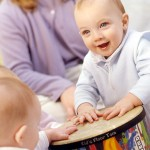 Baby with big smile and floor tom drum